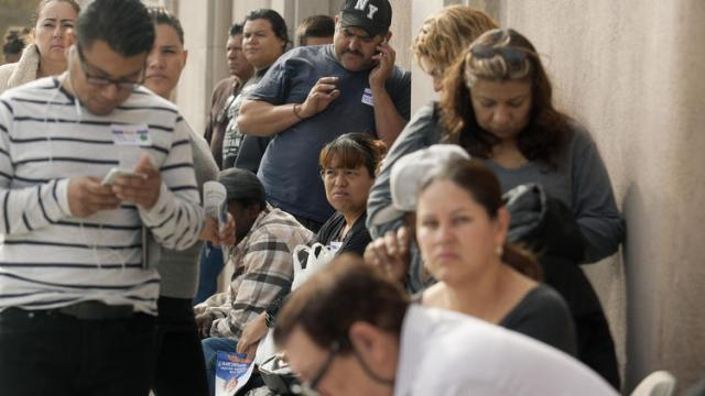 Los Angeles residents line up to enroll in Covered California and Medi-Cal plans on Nov. 15, 2014. The following week, advocates filed suit against the state challenging the legality Medi-Cal's renewal process. (Cheryl Guerrero)
